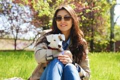 拥抱逗人喜爱的起重器罗素狗小狗的可爱的少妇画象在公园,绿色草坪,叶子背景 行家女性 图库摄影