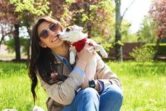 拥抱逗人喜爱的起重器罗素狗小狗的可爱的少妇画象在公园,绿色草坪,叶子背景 行家女性 库存图片