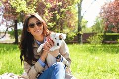 拥抱逗人喜爱的起重器罗素狗小狗的可爱的少妇画象在公园,绿色草坪,叶子背景 行家女性 免版税图库摄影