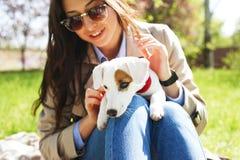 拥抱逗人喜爱的起重器罗素狗小狗的可爱的少妇画象在公园,绿色草坪,叶子背景 行家女性 免版税库存照片