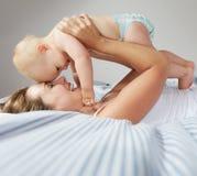 拥抱逗人喜爱的婴孩的愉快的年轻母亲画象  免版税图库摄影