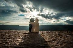 拥抱陶瓷的图夫妇在背景山日落,现出轮廓拥抱和看在背面图的两浪漫人 免版税库存照片