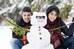 拥抱雪人的微笑的年轻夫妇 库存图片