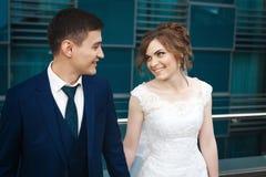 拥抱,微笑和看彼此的新婚佳偶夫妇在餐馆 库存图片