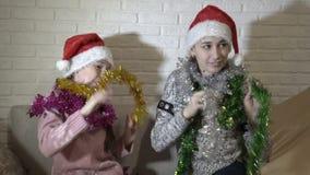 拥抱,笑和演奏在圣诞老人项目和圣诞节闪亮金属片帽子的两少女开会在长沙发的在a 股票录像