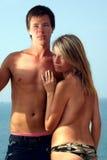 拥抱年轻人的海滩夫妇 免版税库存照片
