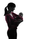 拥抱婴孩剪影的妇女母亲 免版税库存照片
