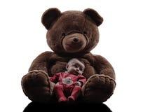 拥抱婴孩坐的剪影的玩具熊 库存照片