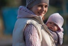 拥抱婴孩的妈妈户外 免版税图库摄影