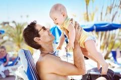拥抱他心爱的儿子的英俊的人 免版税库存照片