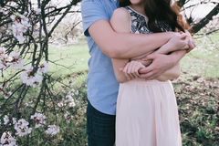 拥抱绽放的手年轻人和妇女一个美丽的女孩从事园艺, 免版税库存照片