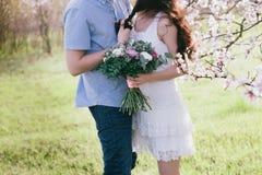 拥抱绽放的手年轻人和妇女一个美丽的女孩从事园艺, 库存照片