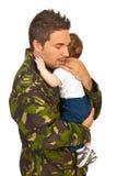 拥抱他新出生的婴孩的军事爸爸 免版税库存照片