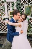 拥抱他新的妻子的愉快的新郎在他们的婚礼以后 特写镜头 免版税库存照片