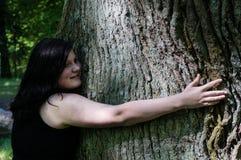 拥抱结构树妇女年轻人 免版税库存照片