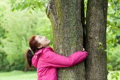 拥抱结构树的女孩 免版税库存图片