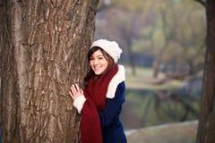 拥抱结构树的美丽的女孩 免版税库存图片