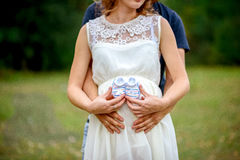 拥抱他白色礼服的丈夫怀孕的妻子 免版税库存图片