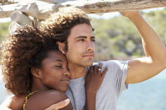 拥抱年轻的夫妇户外,看对照相机的妇女 库存照片