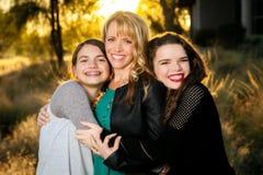 拥抱他们的妈妈的两个青少年的女孩 库存照片