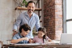 拥抱他的孩子的愉快的父亲,当他们绘画时 图库摄影