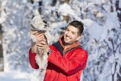 拥抱他的小白色狗的英俊的年轻人在冬天 下雪 库存图片