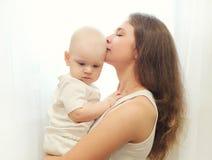 拥抱年轻的母亲亲吻在窗口的婴孩 免版税库存照片