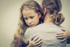 拥抱他的母亲的一个哀伤的女儿画象  免版税库存图片