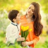 拥抱他的母亲的儿子和给她花 免版税库存照片