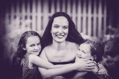 拥抱他们的母亲的女儿-黑白 库存照片