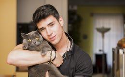 拥抱他的灰色猫宠物的英俊的年轻人 库存图片