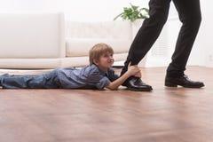 拥抱他的父亲的腿的年轻男孩 免版税库存照片