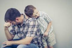 拥抱他的爸爸的哀伤的儿子在墙壁附近 免版税库存照片