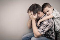 拥抱他的爸爸的哀伤的儿子 库存图片