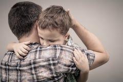 拥抱他的爸爸的哀伤的儿子 图库摄影