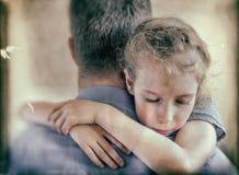 拥抱他的爸爸的哀伤的小女孩 免版税图库摄影