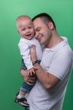拥抱他的男婴的愉快的微笑的父亲 免版税库存图片