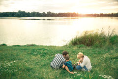 拥抱他们的年轻儿子的年轻美好的父母在日落在湖附近 走沿河的家庭 免版税库存照片