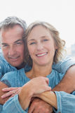 拥抱他的妻子从后面的微笑的人 库存图片