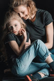 拥抱黑色的微笑的母亲女儿 免版税库存图片