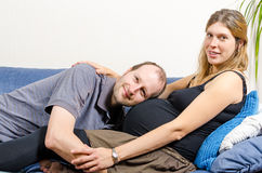 拥抱他长沙发的愉快的丈夫怀孕的妻子 免版税库存照片