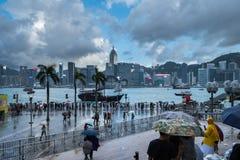 拥挤人民在雨中的等待国庆节烟花显示在香港维多利亚港口江边  免版税库存照片