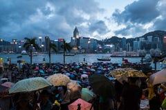 拥挤人民在雨中的等待国庆节烟花显示在香港维多利亚港口江边  图库摄影