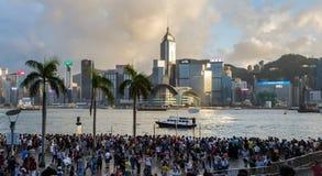 拥挤人民在雨中的等待国庆节烟花显示在香港维多利亚港口江边  免版税库存图片