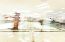 拥挤冲在有精品店的,玻璃橱窗,行动迷离的人们一个现代宽明亮的购物中心大厅里面 免版税库存图片