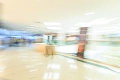 拥挤冲在有精品店的,玻璃橱窗,行动迷离的人们一个现代宽明亮的购物中心大厅里面 库存图片