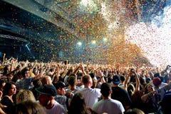 拥挤在音乐会,当投掷从阶段的五彩纸屑在生波探侧器节日时 免版税库存照片
