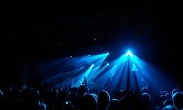 拥挤在黑暗和蓝色光的一个音乐会 库存照片