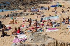 拥挤多岩石的海滩在波尔图,葡萄牙 晒日光浴在沙子的人们 免版税图库摄影