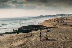 拥挤大西洋夏天海滩在Carcavelos,葡萄牙 免版税库存图片